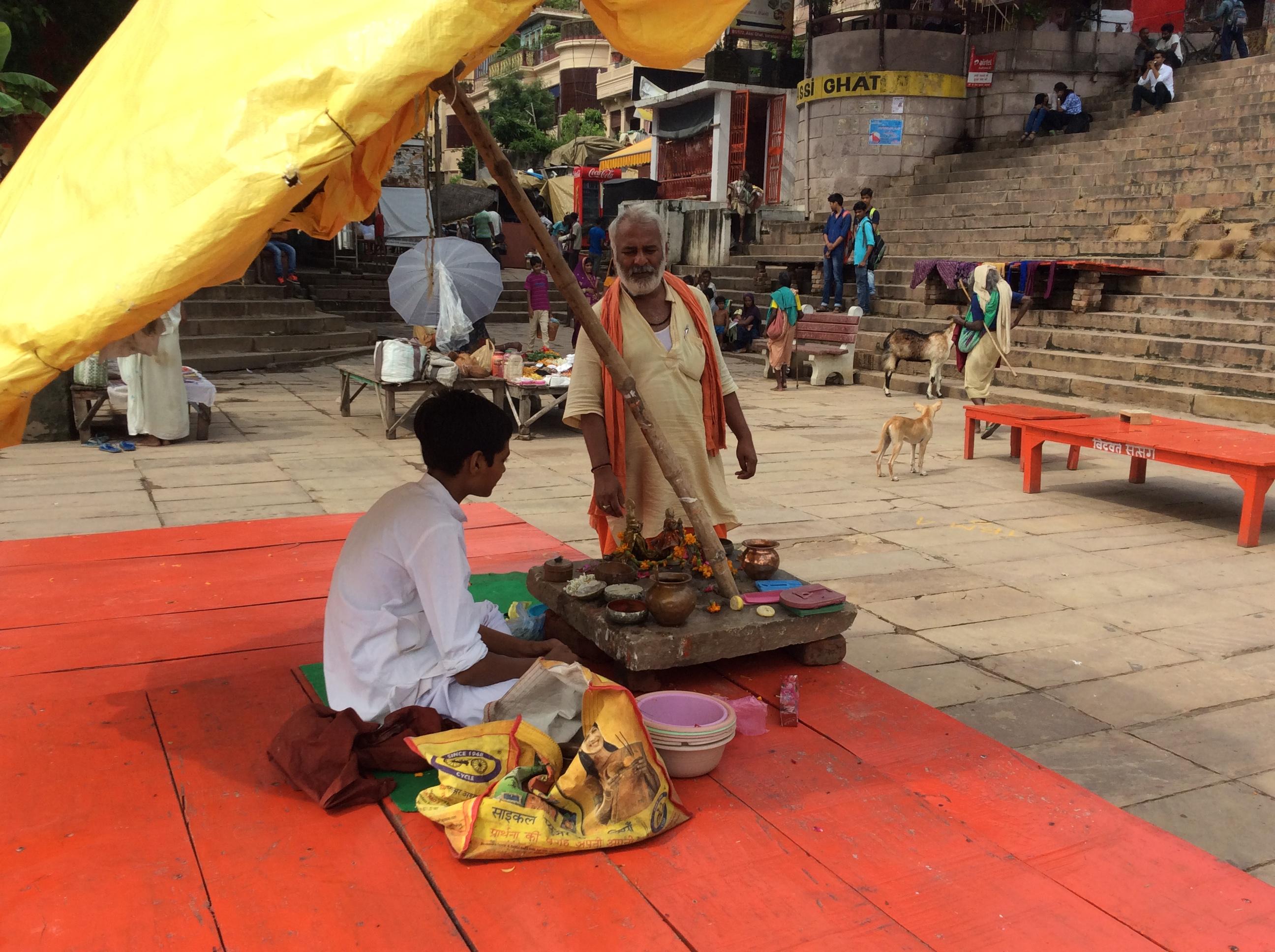 Junger Brahmane verkauft Sandelholzpaste und andere rituelle Pasten