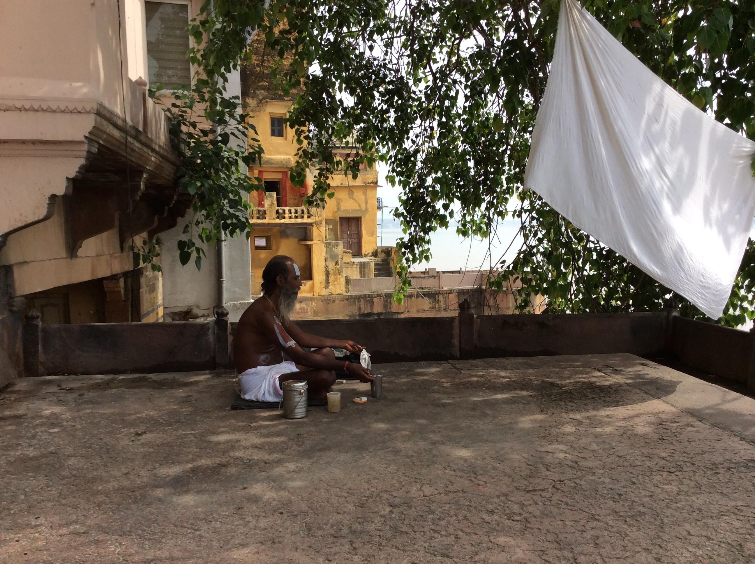 Ein Saddhu meditiert mit Blick auf Mutter Ganges. Das Leintuch vor ihm weht im warmen Wind.