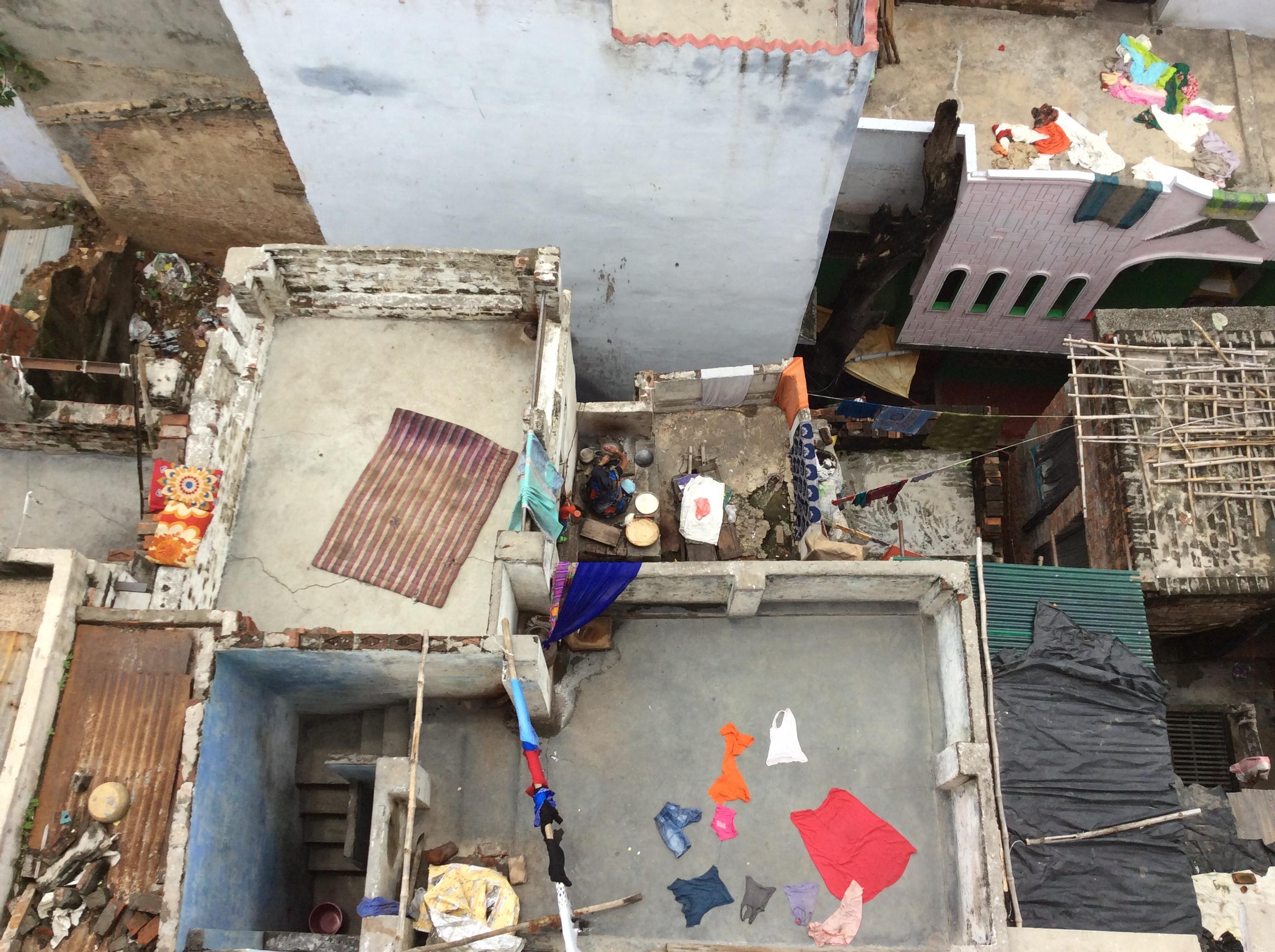 """...eine Frau macht Chapattis auf ihrem Dach. Oft nehmen sie hier, wo viele der """"Unberührbaren"""" wohnen, die als Crematoren arbeiten, die Reste der Scheiterhaufen von den Burning Ghats mit erzählt Ricci und gruselt sich dabei."""