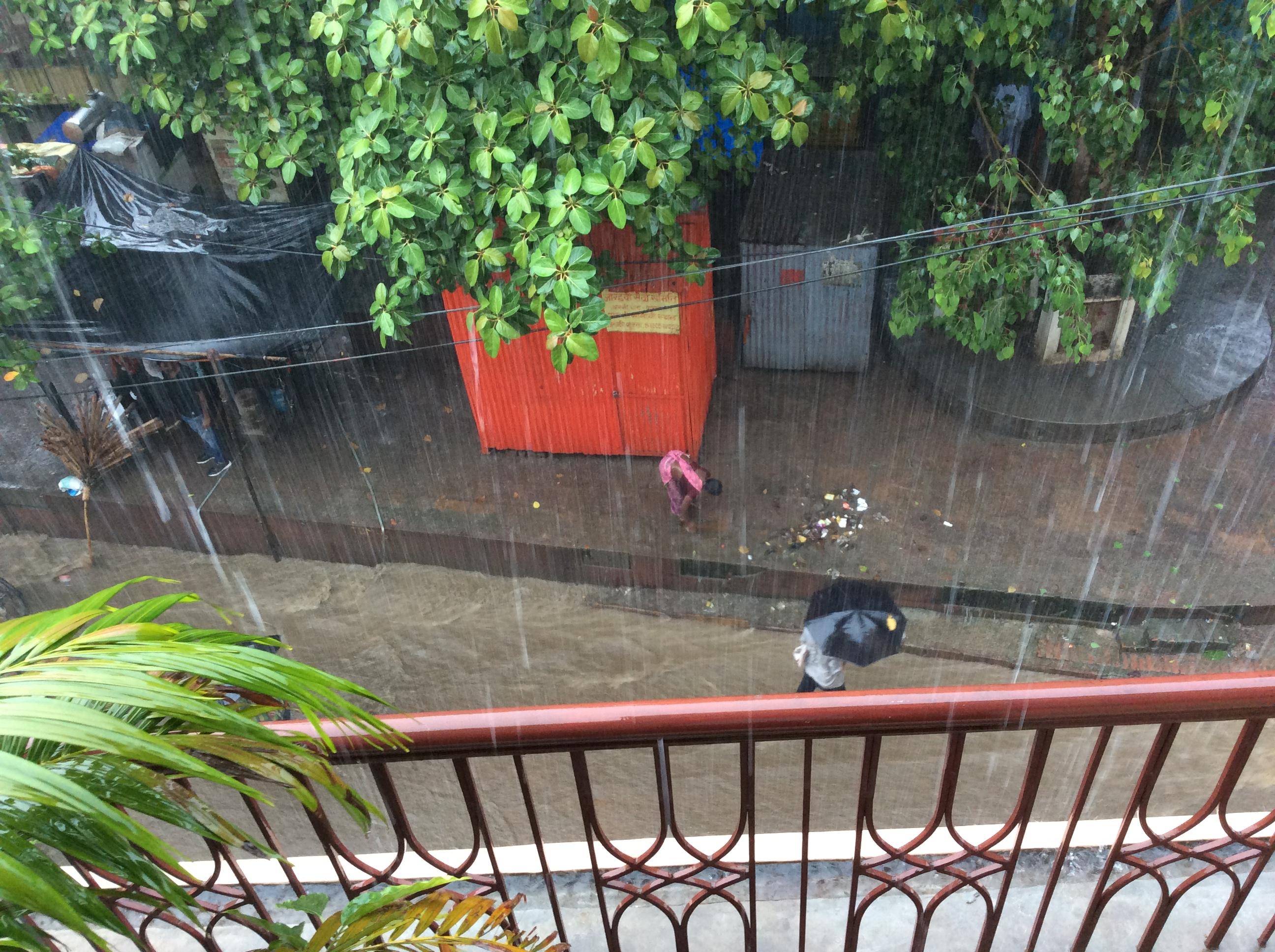 Die Strasse ist zu einem reißenden Fluß geworden. Die Frauen nutzen den Regenguß zum saubermachen.