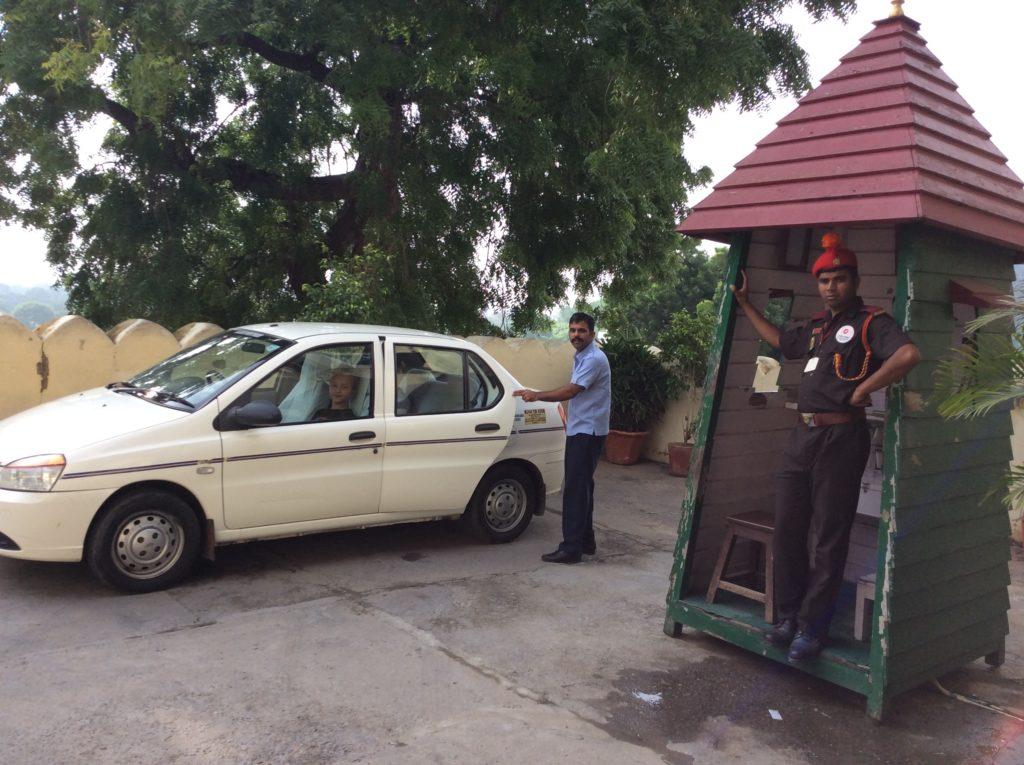 Unser Fahrer Mr. Singh und die Wache mit dem hinreißenden orangenen Federbüschel auf dem Barrett.